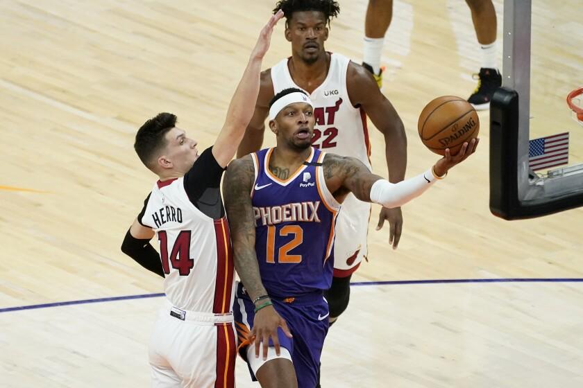 Phoenix Suns forward Torrey Craig (12) shoots past Miami Heat guard Tyler Herro (14) during the first half of an NBA basketball game, Tuesday, April 13, 2021, in Phoenix. (AP Photo/Matt York)