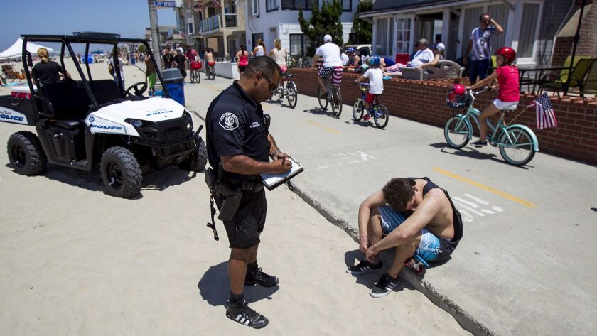 NEWPORT BEACH, JULY 04, 2014 - Vlad Anderson with the Newport Beach Police Department writes a ticke