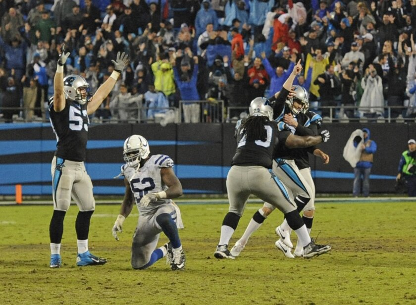 Teammates surround Carolina Panthers kicker Graham Gano (9) after his game-winning field goal in overtime of an NFL football game against the Indianapolis Colts in Charlotte, N.C., early Tuesday, Nov. 3, 2015. (AP Photo/Mike McCarn)