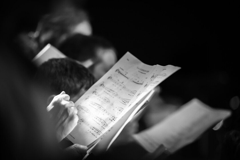 black and white stock photo of hands holding sheet music