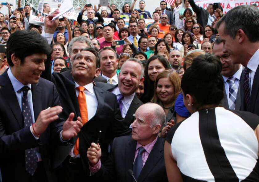 State Sen. Kevin de Leon, from left, Los Angeles City Councilman Gil Cedillo, Senate President Pro Tem Darrell Steinberg and Mayor Eric Garcetti are in a jubilant mood after Gov. Jerry Brown signed a bill signing to allow immigrants lacking legal immigration status to get California driver's licenses.