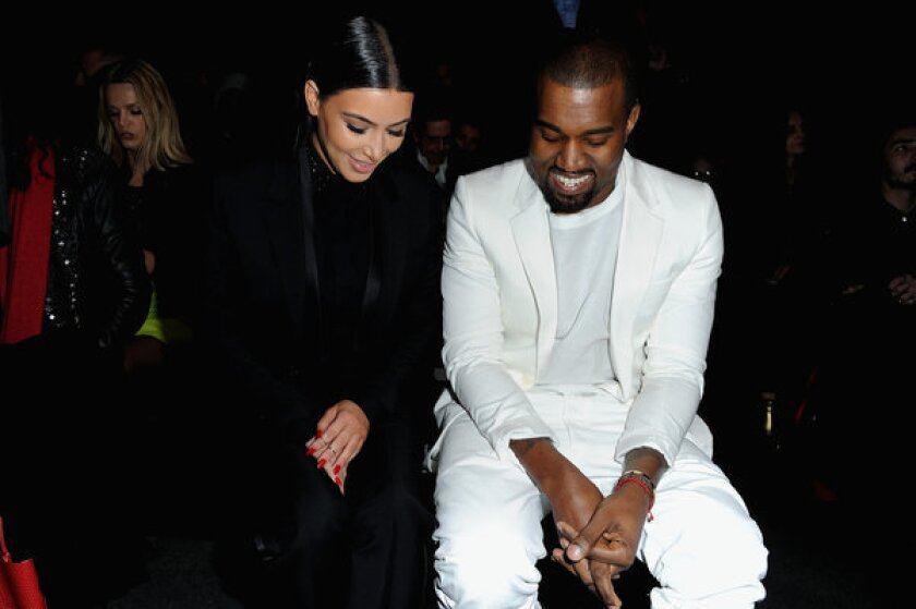 Kim Kardashian and Kanye West share smiles at Givenchy's Fall/Winter 2013 ready-to-wear show during Paris Fashion Week on Sunday.