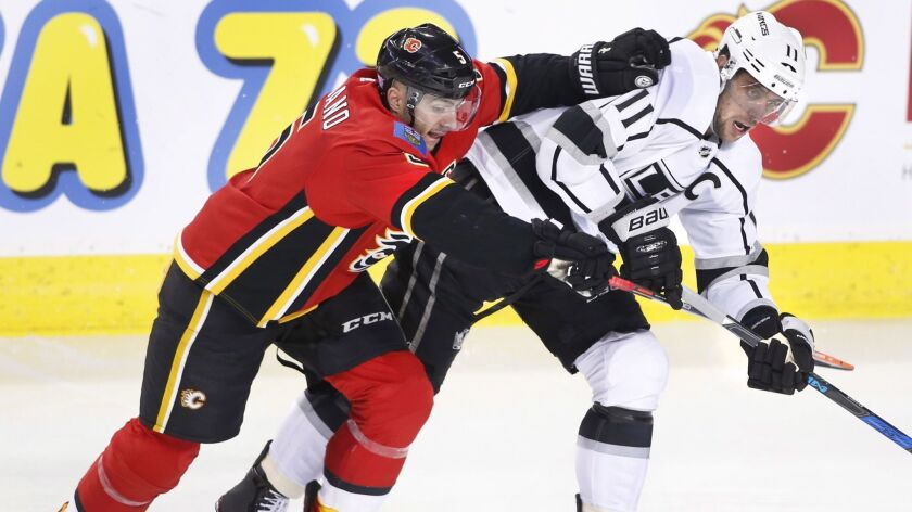 Los Angeles Kings center Anze Kopitar (11) and Calgary Flames defenseman Mark Giordano (5) battle du