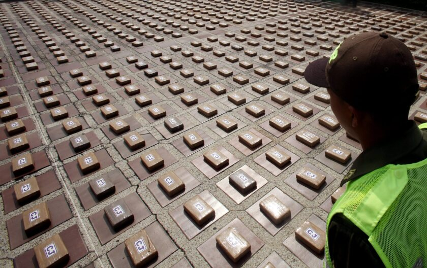 A policeman stands guard during the presentation of 1,450 pounds of cocaine confiscated from two trucks in Cali, Colombia. According to authorities, the cocaine belonged to the Urabeños drug trafficking gang.