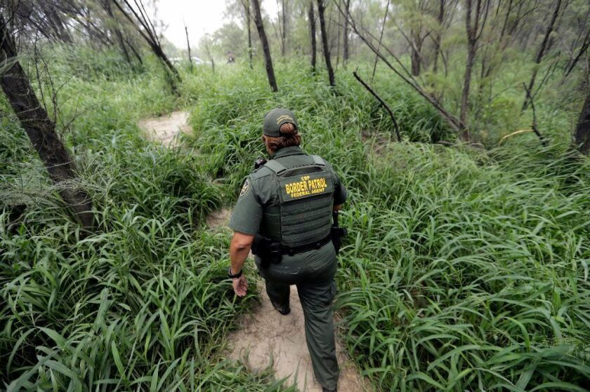 Border Patrol agent walks along a path near the banks of the Rio Grande River near McAllen, Texas.
