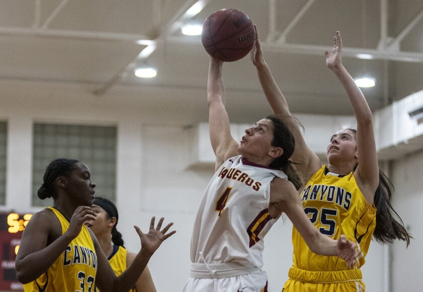 Glendale Community College guard Vicky Oganyan grabs a rebound between College of the Canyons' Diamyn Davis and Cristian Patron, right, during a game Feb. 12.