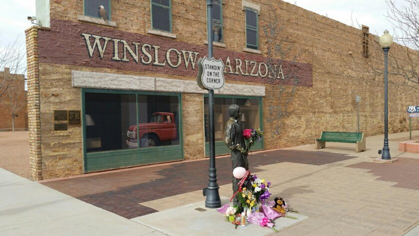 "In this Tuesday, Jan. 19, 2016, photo courtesy of Tom McCauley,  the corner in Winslow, Ariz., made famous by the 1972 Eagles' song ""Take it Easy."" Fans are leaving flowers, hand-written notes and candles at the site to celebrate the life of Eagles band member Glenn Frey. Frey died Monday, Jan. 18."