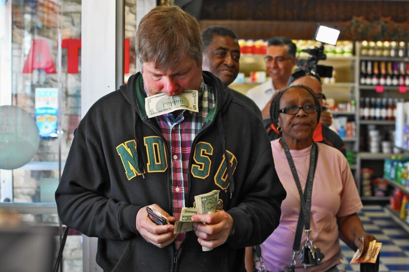 Mark Boesen stands in line to purchase Powerball lottery tickets at Bluebird Liquor store in Hawthorne Wednesday morning.