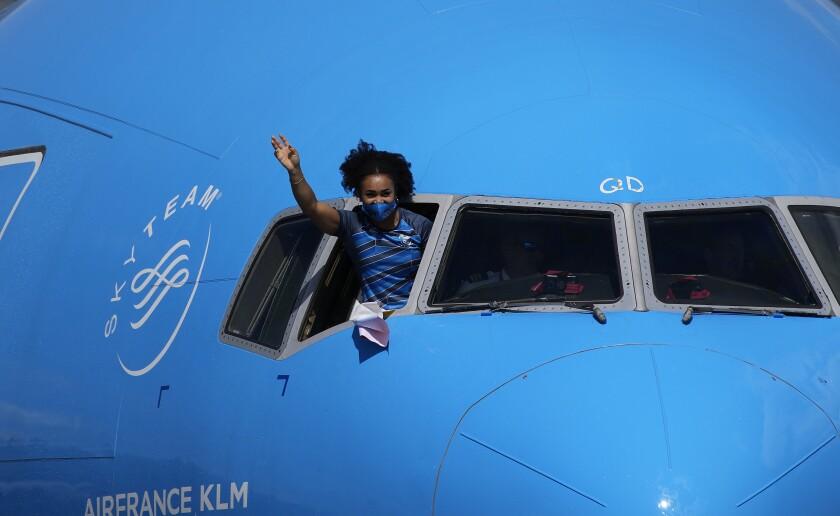 Neisi Dajomes Barrera, pesista ecuatoriana que ganó el oro en los 76 kilogramos durante los Juegos Olímpicos de Tokio, saluda desde la cabina de un avión, a su regreso a Quito, el miércoles 4 de agosto de 2021 (AP Foto/Dolores Ochoa)