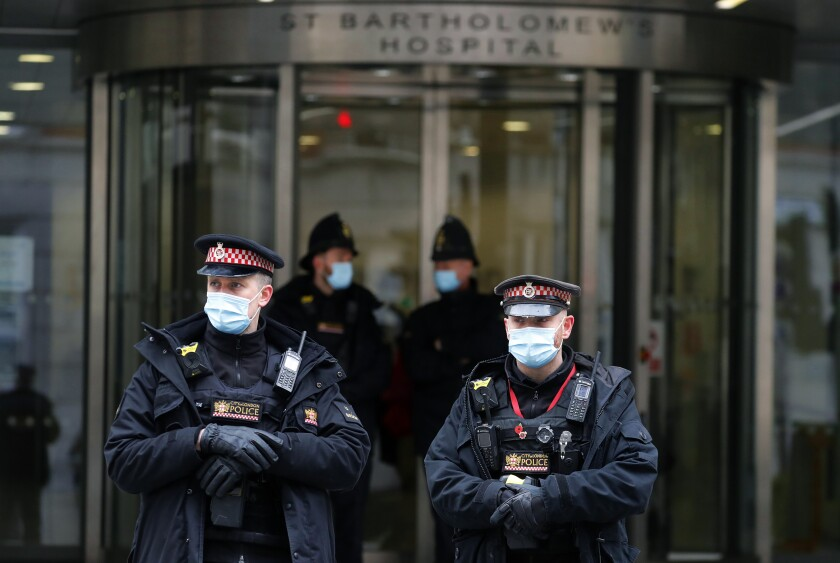 """Police officers stand outside the main entrance of St Bartholomew's Hospital where Britain's Prince Philip is being treated in London, Friday, March 5, 2021. Buckingham Palace says Prince Philip has had a successful heart procedure in a London hospital. The palace says the 99-year-old Duke of Edinburgh, the husband of Queen Elizabeth II, """"underwent a successful procedure for a pre-existing heart condition at St Bartholomew's Hospital."""" (AP Photo/Frank Augstein)"""