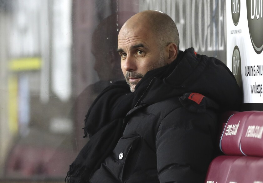 Manchester City's head coach Pep Guardiola looks on before the English Premier League soccer match between Burnley and Manchester City at Turf Moor stadium in Burnley, England, Wednesday, Feb. 3, 2021. (Martin Rickett/Pool via AP)