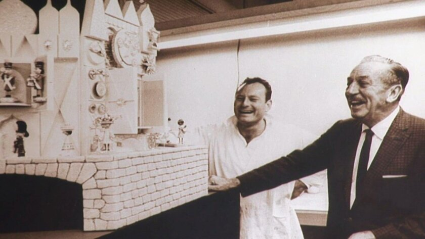 "Screen grab from ""The Whimsical Imagineer"" shows Rolly Crump, left, and Walt Disney reviewing a model Crump's clock on the exterior of the ""It's A Small World"" ride, which opened six months before Disney's death in 1966."