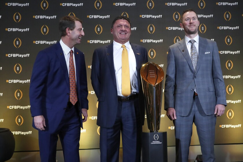 Clemson head coach Dabo Swinney, left, jokes with LSU head coach Ed Orgeron and Oklahoma head coach Lincoln Riley, right, as they pose with the College Football Championship trophy during a news conference ahead for the College Football playoffs Thursday, Dec. 12, 2019, in Atlanta. Ryan Day of Ohio State was unable to attend. (AP Photo/John Bazemore)