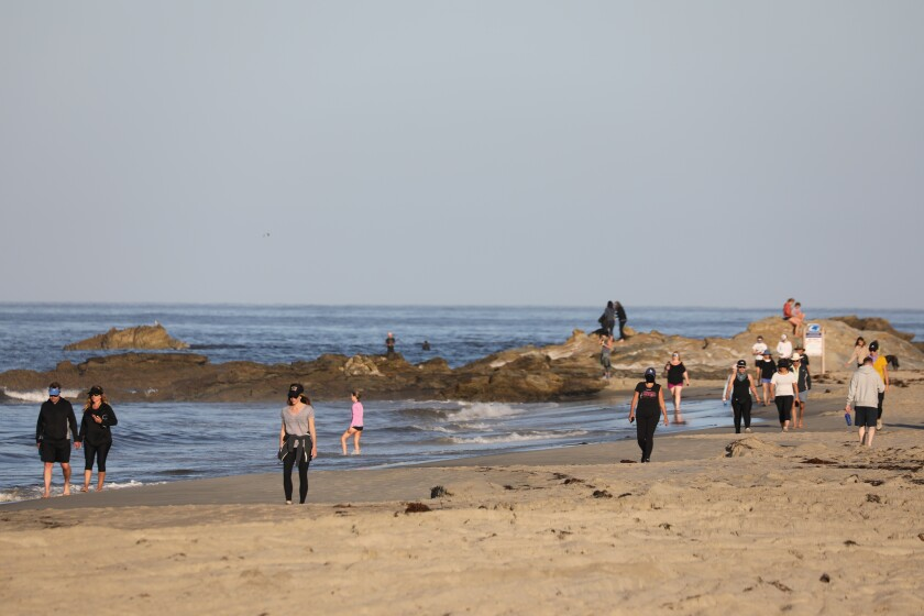 People stroll along the coast in Laguna Beach on Tuesday morning.