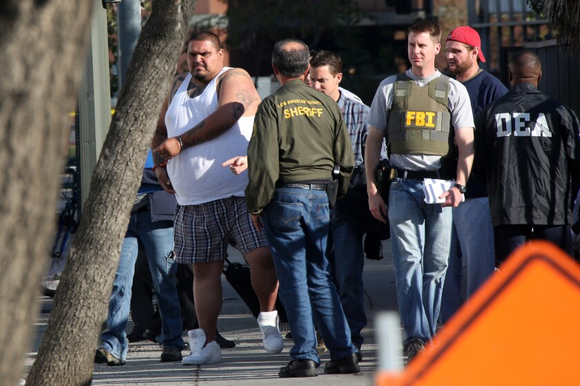 A suspect is processed in downtown Los Angeles on Wednesday as authorities round up members of the Big Hazard gang indicted under federal RICO statutes.