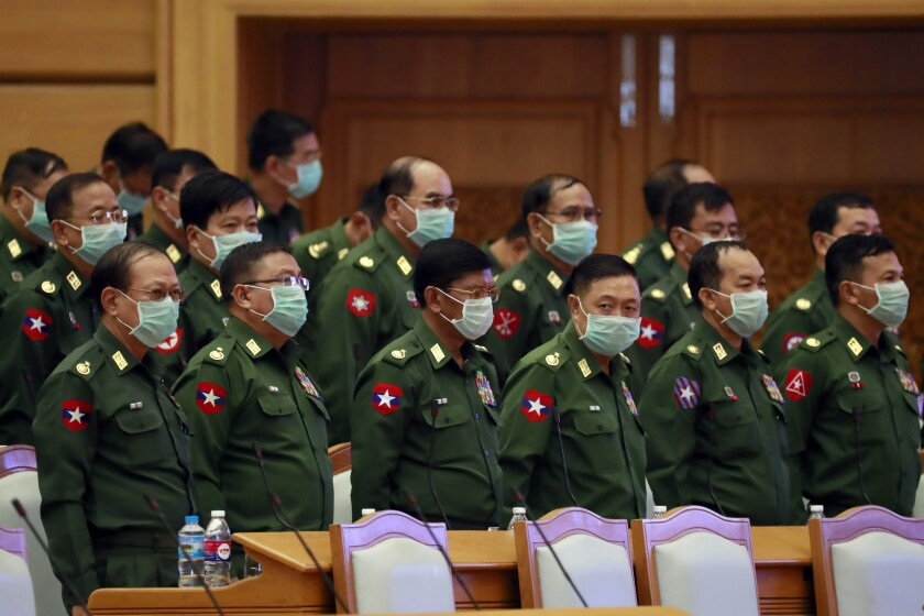 Military representatives stand upon arrival of Parliament Chairman T Khun Myat during a regular session of the Union Parliament Wednesday, March. 11, 2020, in Naypyitaw, Myanmar. (AP Photo/Aung Shine Oo)