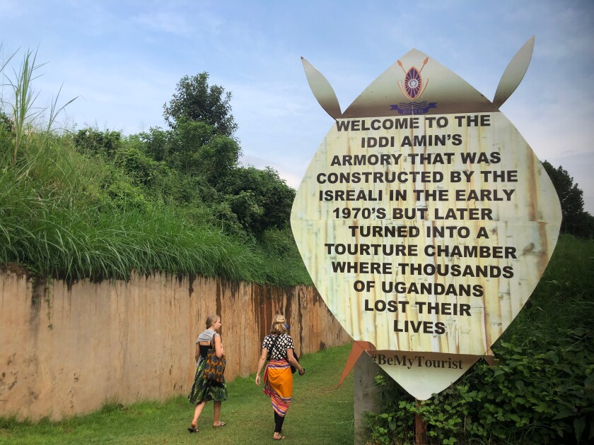 Tourists walk into a bunker in Kampala where leader Idi Amin sent political opponents to die.