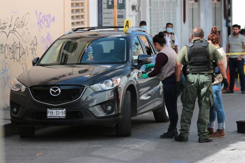 Policías ministeriales recaban información en torno al automóvil donde viajaba la exfiscal del estado de Guerrero Martha Elba Garzón Bernal, quien fue atacada a balazos hoy, viernes 1 de diciembre de 2017, durante un presunto asalto en el centro de Chilpancingo (México). EFE