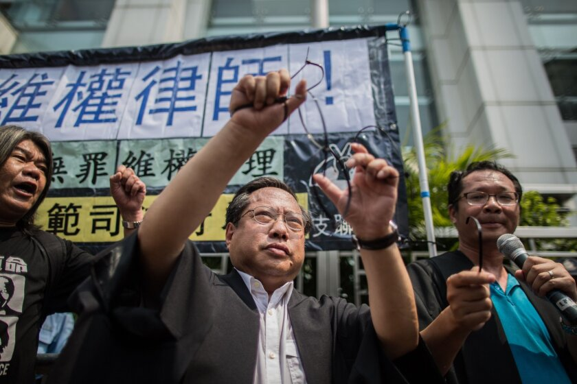 """Hong Kong Democratic Party's Albert Ho (C) releases himself from mock hand cuffs as he and legislator Leung Kwok-hung (L), known as """"Long Hair"""", attend a protest in Hong Kong on July 12, 2015, after at least 50 Chinese human rights lawyers and activists were detained or questioned in recent days in an """"unprecedented"""" police swoop, rights groups said on July 11."""