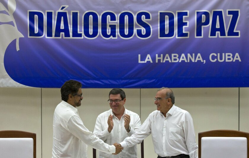 Humberto de la Calle, right, head of Colombia's government peace negotiation team, shakes hands with Ivan Marquez, chief negotiator of the Revolutionary Armed Forces of Colombia, left, while Cuban Foreign Minister Bruno Rodriguez, center, applauds after signing an agreement in Havana, Cuba, Wednesd