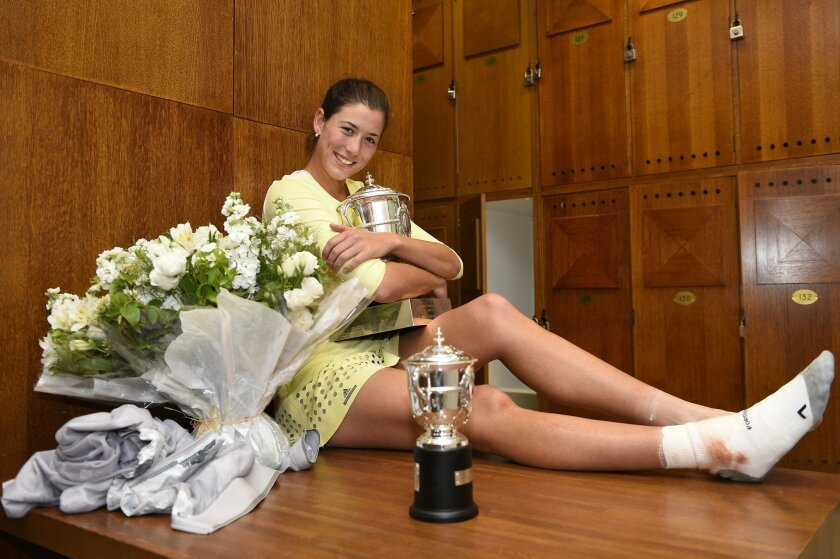 Spain's Garbine Muguruza holds her cup in the dressing room after defeating Serena Williams of the U.S. in the women's final of the French Open tournament at the Roland Garros stadium in Paris, Saturday, June 4, 2016 (Corinne Dubreuil, Pool via AP)