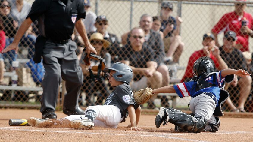 Costa Mesa American's Jude Dravecky slides in safely passed the tag attempted by Costa Mesa National