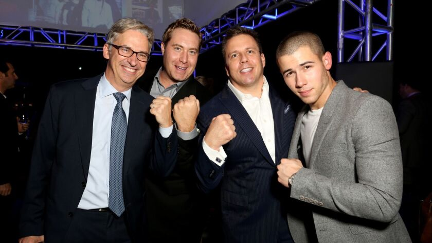 "Daniel York, left, shown with AT&T executives Bart Peters and Chris Long, celebrate the season premiere of DirecTV's ""Kingdom"" with actor Nick Jonas, right, in West Hollywood in 2015."