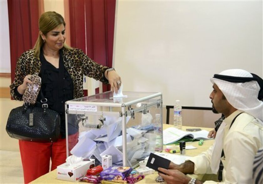A Kuwaiti citizen casts her vote at a polling station in Saalwa, Kuwait on Saturday, Dec. 1, 2012. The general election to appoint a new Parliament is the fifth since mid-2006, and the second this year.(AP Photo/Gustavo Ferrari)