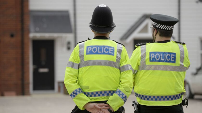 British police officers stand facing a residential property in Amesbury, England, on July 4 after two people were exposed to an unknown substance.