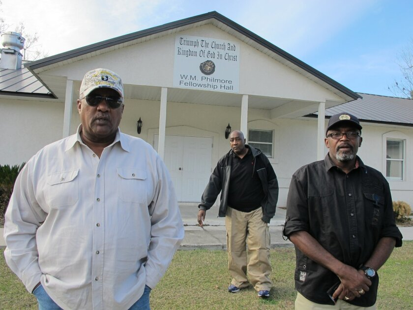 In this Thursday, Dec. 18, 2014 photo, Alonzo Philmore, left, Harry Campbell, center, and Suwannee County NAACP president Leslie White stand in front of their church in Live Oak, Fla.  In 1952 a wealthy black woman named Ruby McCollum was found guilty by an all-male, white jury for the murder of a