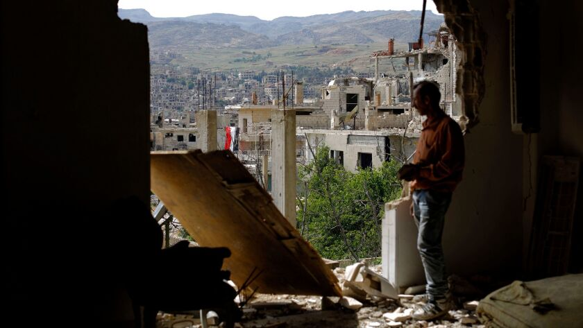 A man surveys damage in a town outside Damascus on May 18. About 400,000 people have died in Syria's six-year-old civil war.