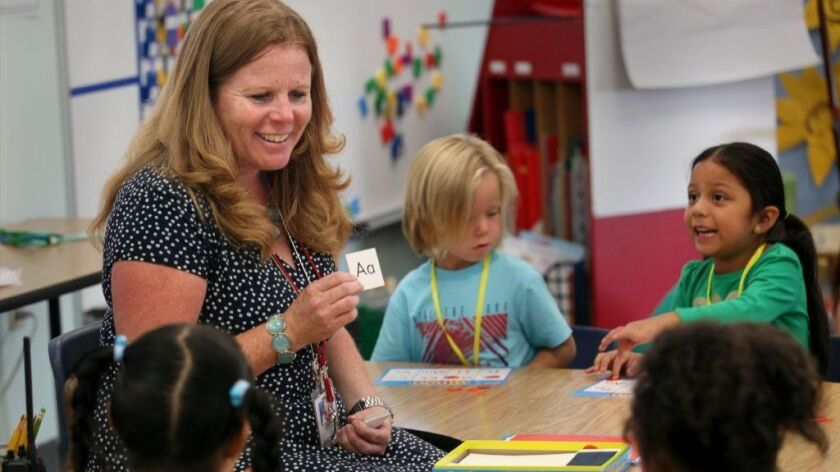 In this 2016 photo, Rachel D'Ambroso, then the principal of Breeze Hill Elementary School in Vista, leads transitional kindergarten students in a game of bingo using the alphabet. A North County mother is pushing to make transitional kindergarten mandatory for all districts.