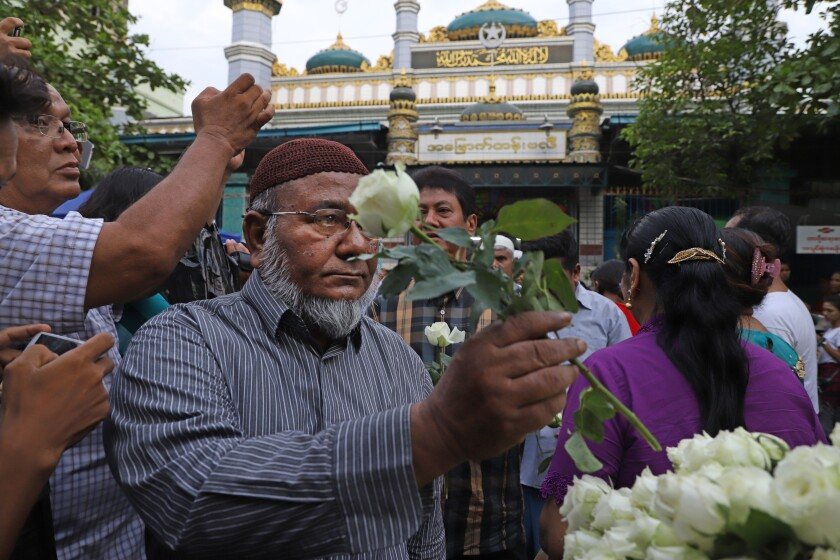 Muslims receive white roses from Buddhists at Joon Mosque in Mandalay on May 30, 2019, as part of a campaign promoting religious harmony.