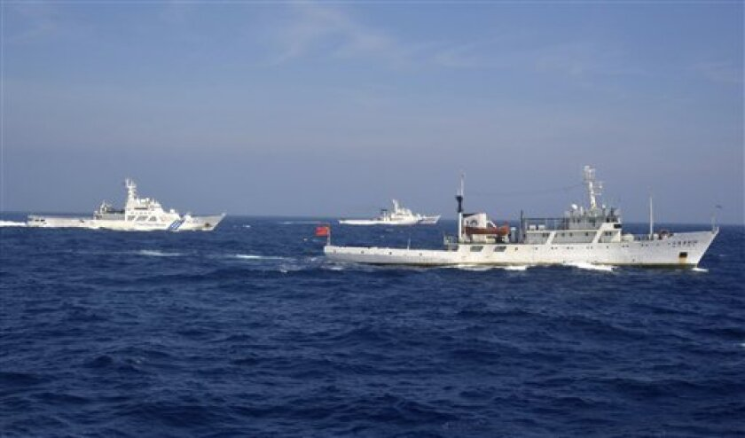 In this photo released by China's Xinhua News Agency, a Chinese patrol ship, right, encounters Japanese Coast Guard vessels near the disputed islands in the East China Sea, called the Senkaku in Japan and Diaoyu in China, Wednesday, July 11, 2012. Japan's government is negotiating to buy the disput