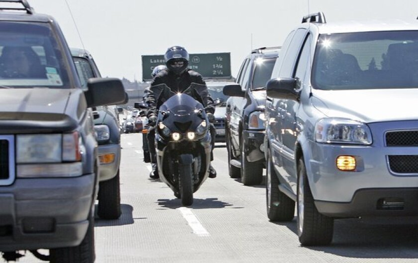 Riders split lanes between cars on the southbound 405 in Long Beach.