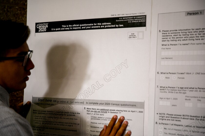 A volunteer hangs up a sample copy of the 2020 Census at a workshop