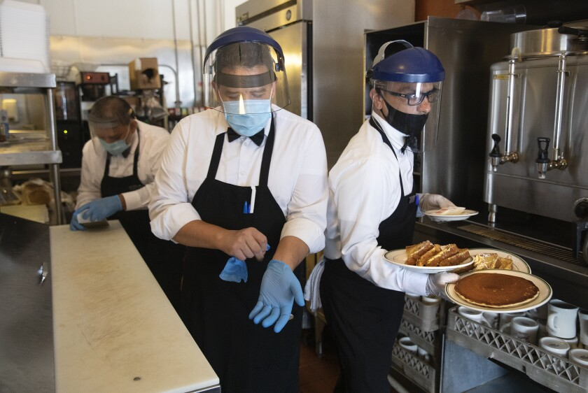 Waiters with breakfast plates at the Original Pantry in downtown Los Angeles.