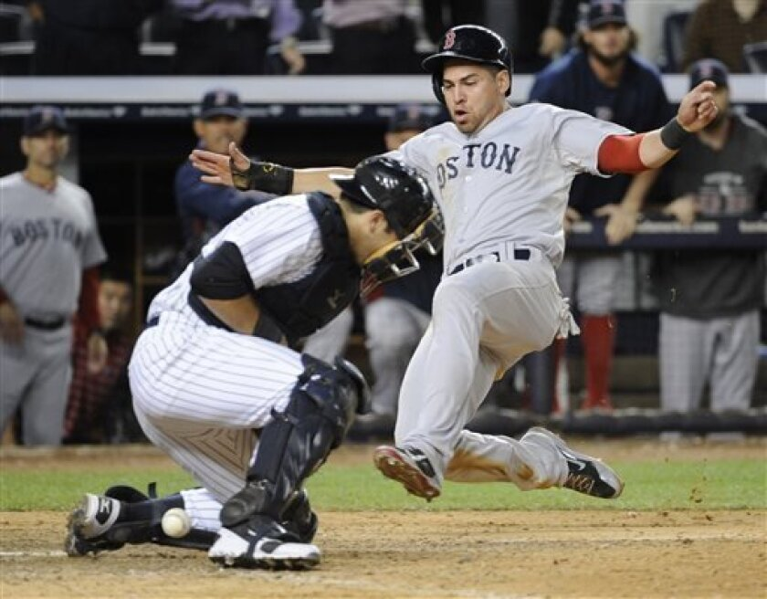 Boston Red Sox's Jacoby Ellsbury, right, scores on a single by Shane Victorino for the go-ahead run as New York Yankees catcher Austin Romine cannot handle the throw during the 10th inning of a baseball game Thursday, Sept. 5, 2013, at Yankee Stadium in New York. The Red Sox defeated the Yankees 9-