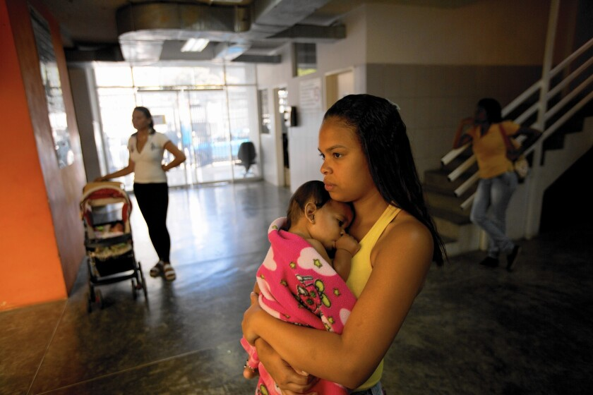 Awoman holds her sick baby as she waits to see a doctor at a medical center in Caracas, Venezuela on Feb. 11.