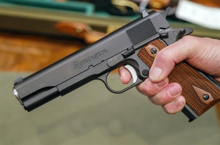 Un vendedor sostiene una pistola de la compañía estadounidense Remington expuesta en una tienda en Atlanta, Georgia (Estados Unidos), el 13 de febrero de 2018. EFE/Archivo