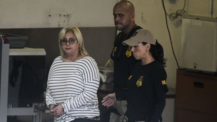 Federal agents escort former Puerto Rico Health Insurance Administration head Ángela Ávila-Marrero w