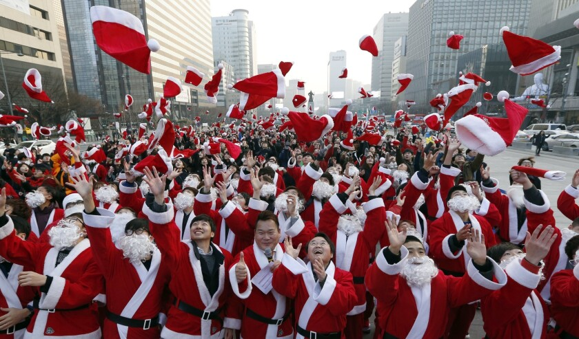 Hundreds of volunteers clad in Santa Claus costumes throw their hats in the air during a Christmas c