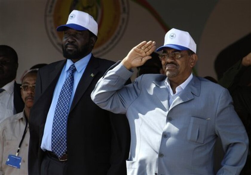 In this photo released by the United Nations Mission in Sudan (UNMIS), Sudanese President Omar al-Bashir, right, and Sudanese Vice-President and southern leader Salva Kiir, left, are seen during a military parade marking the fourth anniversary celebration of the signing of the Comprehensive Peace A