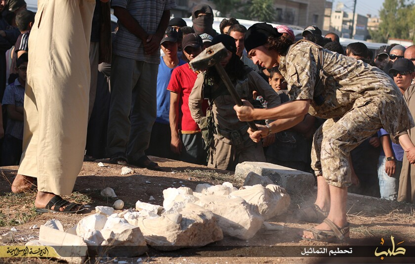 In this image posted on a militant website by Islamic State on July 3, a man is shown smashing archaeological pieces from the ancient site of Palmyra, Syria. The image has been verified and is consistent with reporting by the Associated Press.