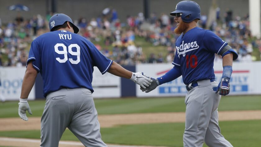The Dodgers' Justin Turner is congratulated by pitcher Hyun-Jin Ryu after Turner's home run in a spring training game against the Brewers on Thursday in Phoenix.