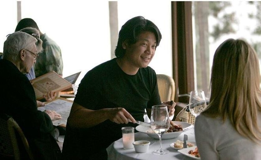 Alex Lee of La Jolla dines with Cristina Simons of Santa Monica at Trattoria Acqua in La Jolla. The restaurant has lowered prices and added comfort foods to its upscale menu.