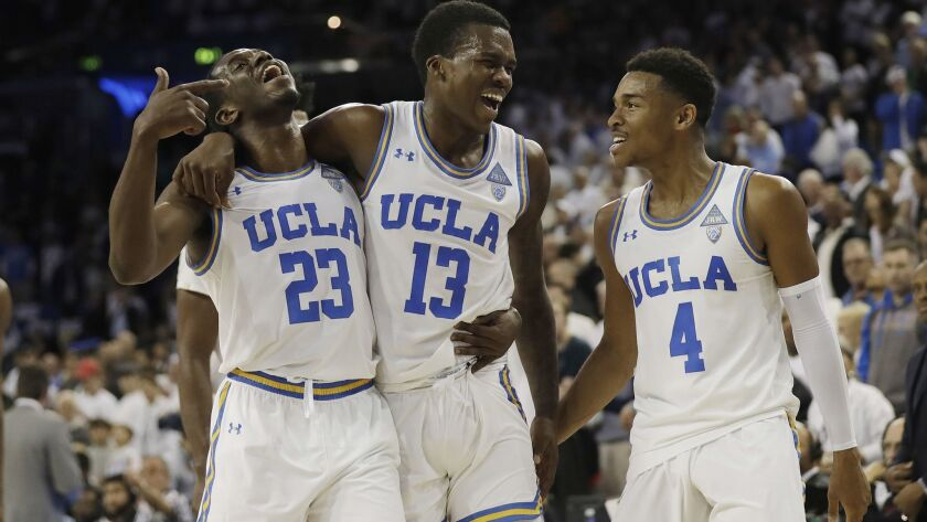 UCLA guard Kris Wilkes (13) celebrates after scoring the go-ahead basket with teammates Prince Ali (23) and Jaylen Hands (4) during a game against Notre Dame on Dec. 8. UCLA won 65-62.