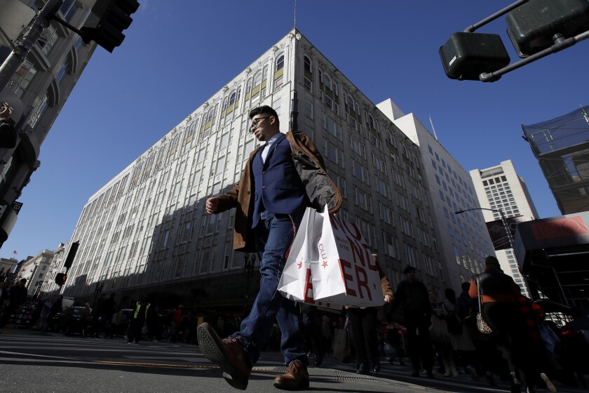 FILE - In this Nov. 29, 2019, file photo, man carries shopping bags across the street from a Macy's store in San Francisco. Macy's says it is closing 125 of its least productive stores and cutting 2,000 corporate jobs as the struggling department store tries to reinvent itself in the age of online shopping. The moves announced Tuesday, Feb. 4, 2020, come ahead of Macy's annual investor meeting where CEO Jeff Gennette is expected to unveil a three-year reinvention plan. (AP Photo/Jeff Chiu, File)