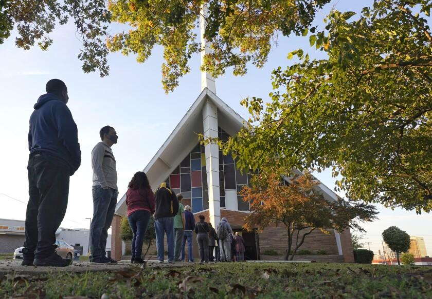 Fotografía de votantes haciendo fila frente a la Iglesia Bautista Vickery para votar en Dallas.
