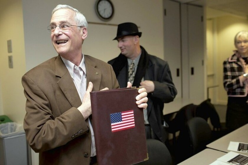 Howard Epstein, vice chairman of communications for the San Francisco Republican Party, holds up his binder with an American flag for the Pledge of Allegiance as a party meeting gets underway at Milton Marks Conference Center in the city.